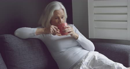 plavé vlasy : Side view of a thoughtful senior Caucasian woman drinking coffee on a sofa