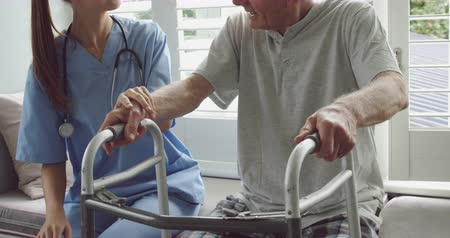 atender : Front view close up of a senior Caucasian man using a walking frame and young Caucasian female doctor in a hospital Archivo de Video