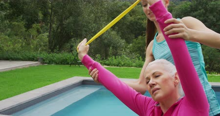 visszavonulás : Front view close up of a senior Caucasian woman exercising with a rubber band in a garden, with a young Caucasian female fitness instructor and a swimming pool in the background Stock mozgókép