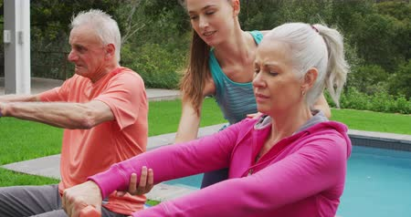 отступление : Side view close up of a senior Caucasian woman and man exercising with dumbbells in a garden, with a young Caucasian female fitness instructor and swimming pool behind them