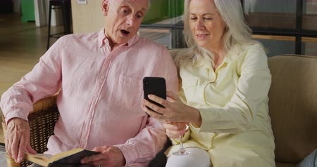 retiro : Front view of a senior Caucasian woman and man sitting on a couch and using a smartphone