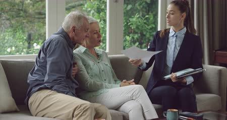 panoya : Front view of a senior Caucasian man and woman in a sitting room at a meeting with a young Caucasian female financial advisor Stok Video
