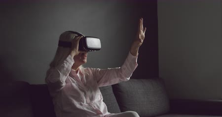 spare : Side view close up of a senior Caucasian woman wearing a VR headset and reaching with her hands out