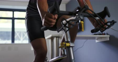 um : Front view close up of a young mixed race male cyclist using a metabolic gas analyser during training, wearing a face mask