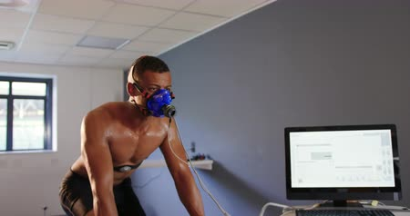 estacionário : Front view of a young mixed race male cyclist using a metabolic gas analyser during training, wearing a face mask with a computer monitor next to him