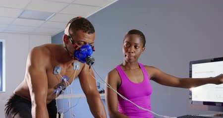 midiendo : Front view of a young mixed race male cyclist using a metabolic gas analyser during training, wearing a face mask while a young African American female personal trainer is holding a tablet and checking results on a computer screen Archivo de Video