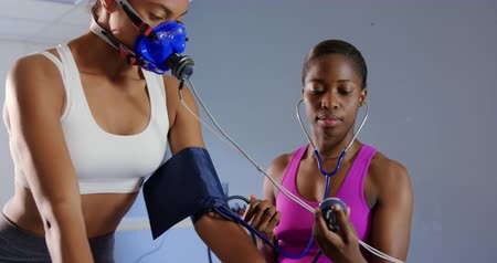 инструктор : Front view close up of a young mixed race female cyclist using a metabolic gas analyser during training, wearing a face mask while a young African American female personal trainer is checking her blood pressure