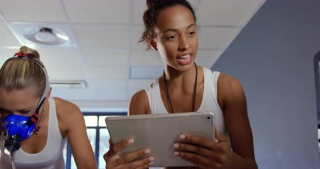 estacionário : Front view close up of a young Caucasian female cyclist using a metabolic gas analyser during training, wearing a face mask while a young mixed race female personal trainer is holding a tablet and checking results on a computer screen