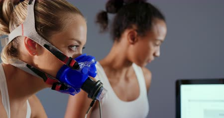 instrutor : Side view close up of a young Caucasian female cyclist using a metabolic gas analyser during training, wearing a face mask while a young mixed race female personal trainer is checking results on a computer screen