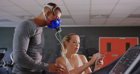 treadmill : Side view of a young mixed race man running on a treadmill and using a metabolic gas analyser during training while a young Caucasian female personal trainer is checking results on a tablet