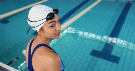 dosažení : Side view of a young mixed race female swimmer by a swimming pool, smiling to camera Dostupné videozáznamy