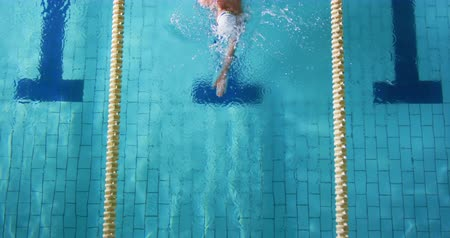 calções de banho : Overhead view of a young Caucasian male swimmer training in a swimming pool, crawl