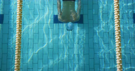 calções de banho : Overhead view of a young Caucasian male swimmer training in a swimming pool, diving and emerging from water