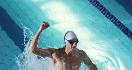 calções de banho : Front view of a young Caucasian male swimmer training in a swimming pool, emerging from water, smiling and punching the air
