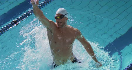 plavat : Front view of a young Caucasian male swimmer training in a swimming pool, emerging from water, smiling and punching the air