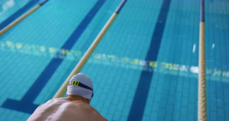 calções de banho : Rear view close up of a young Caucasian male swimmer training in a swimming pool, jumping into water