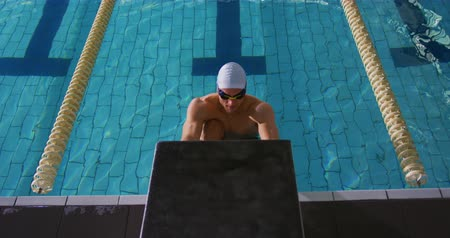 calções de banho : Front view of a young Caucasian male swimmer training in a swimming pool, pushing off the wall Vídeos