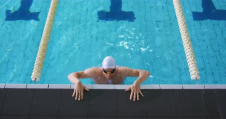 calções de banho : Front view of a young Caucasian male swimmer training in a swimming pool, getting out of the swimming pool