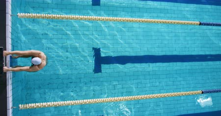 calções de banho : Overhead view of a young Caucasian male swimmer training in a swimming pool, pushing off the wall to swim backstroke