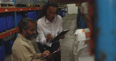 inspecting : Side view close up of a young mixed race female warehouse manager and a middle aged mixed race male warehouse worker holding clipboards, inspecting shelves and talking in a storage warehouse
