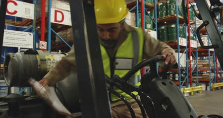holding onto : Front view close up of a middle aged mixed race male warehouse worker holding a clipboard climbing onto a forklift truck in a warehouse loading bay Stock Footage