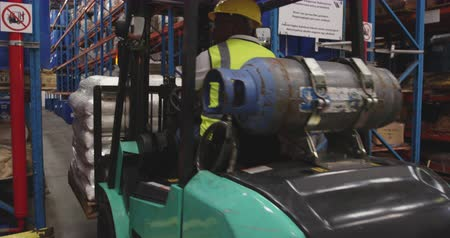 vorkheftruck : Rear view close up of an African American young male warehouse worker driving a forklift truck reversing with sacks of goods in a warehouse loading bay