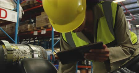 holding onto : Front view close up of a young mixed race female warehouse worker using a tablet computer climbing onto a forklift truck in a warehouse loading bay