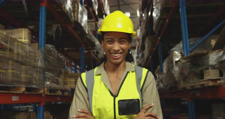 vest : Portrait close up of a young mixed race female warehouse worker wearing a yellow hard hat standing with her arms crossed, looking to camera smiling in a storage warehouse