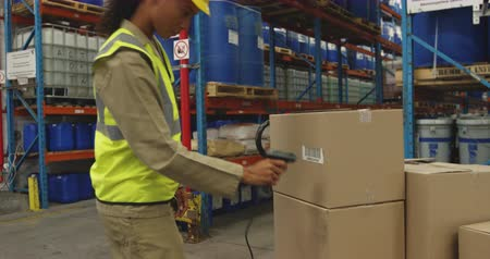 čtenář : Side view close up of a young mixed race female warehouse worker scanning a label on a box with a barcode reader in a warehouse loading bay and then carrying the box away