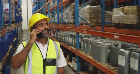 vest : Side view close up of a smiling middle aged mixed race male warehouse worker wearing a hard hat looking up at shelves talking on a smartphone in a storage warehouse, with a male worker busy working in the background