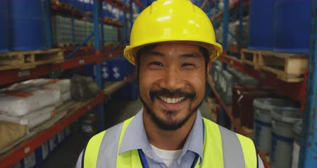 yelek : Portrait close up of a young Asian male warehouse worker wearing a yellow hard hat looking to camera smiling in a storage warehouse Stok Video