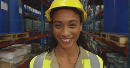 жилет : Portrait close up of a young mixed race female warehouse worker wearing a yellow hard hat looking to camera smiling in a storage warehouse