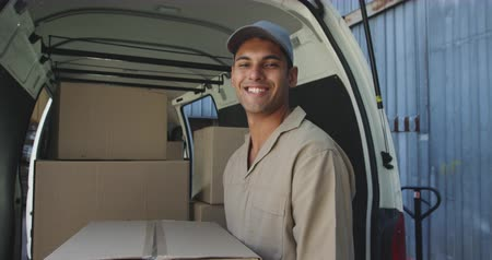 beside : Portrait close up of a young mixed race male warehouse worker holding a box and smiling to camera standing beside the back of an open van full of boxes outside a warehouse