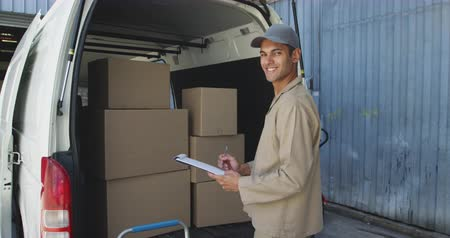 crate : Portrait of a young mixed race male warehouse worker standing, holding a clipboard and smiling to camera by the back of an open van full of boxes outside a warehouse