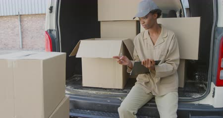 deposito : Front view close up of a young mixed race female warehouse worker sitting in the back of an open van full of boxes, writing on a clipboard outside a warehouse loading area