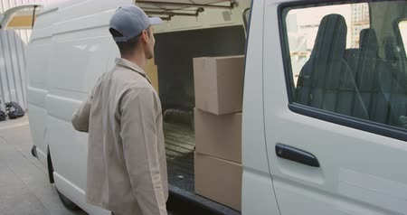 バン : Side view of a young mixed race man opening the side door of a van full of boxes, turning to face the camera, crossing his arms and smiling outside a warehouse