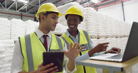generation z : Portrait close up of a young Caucasian male warehouse manager using a tablet computer talking with a young mixed race female warehouse manager using a laptop computer at a standing desk in a warehouse, both smiling
