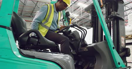 vorkheftruck : Side view close up of a middle aged mixed race male warehouse worker climbing on to a forklift truck in a warehouse loading bay