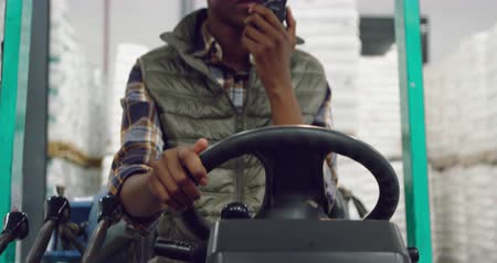 harde schijf : Front view close up of a young mixed race female warehouse worker driving a forklift truck ad talking on a two-way radio in a warehouse loading bay