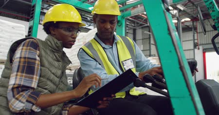 vorkheftruck : Side view close up of a young mixed race female warehouse worker holding a clipboard and a middle aged mixed race male warehouse worker driving a forklift truck talking in a warehouse loading bay