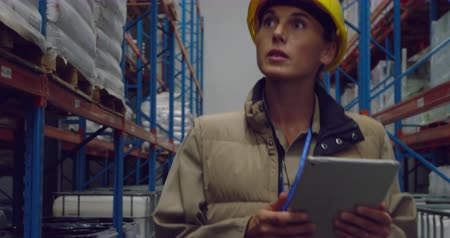concentrando : Front view close up of a young Caucasian female warehouse manager using a tablet computer and inspecting shelves in a storage warehouse