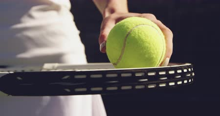 tennis whites : Close up mid section of a young Caucasian woman holding a racket and a ball