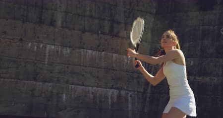 tennis whites : Front view of a young Caucasian woman playing tennis on a court, returning a ball