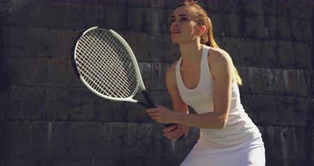 tennis whites : Front view close up of a young Caucasian woman playing tennis on a court, returning a ball