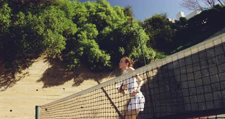 beyazlar : Side view of a young Caucasian woman playing tennis on a court, returning a ball Stok Video