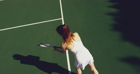 tennis whites : Overhead view of a young Caucasian woman playing tennis on a court, serving Stock Footage
