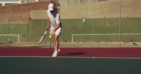 beyazlar : Front view of a young Caucasian man playing tennis on a court, bouncing a ball preparing to serve Stok Video