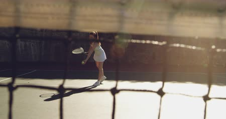 teniszütő : Front view of a young Caucasian woman playing tennis on a court, bouncing a ball preparing to serve, seen through a net Stock mozgókép