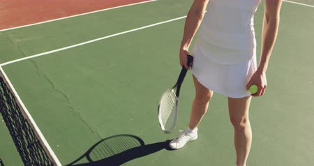 tennis whites : Front view low section of a young Caucasian woman playing tennis on a court, holding a ball and swinging a racket