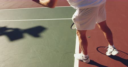 tennis whites : Side view close up of a young Caucasian man playing tennis on a court, bouncing a ball preparing to serve Stock Footage